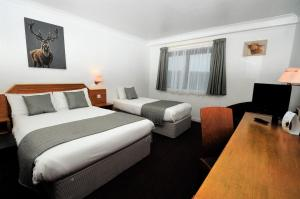 A bed or beds in a room at Days Inn Hamilton