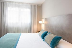 A bed or beds in a room at Hotel & Spa Real Jaca