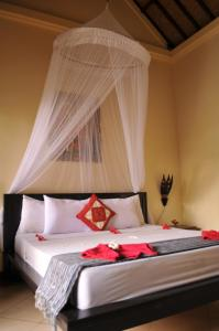 A bed or beds in a room at Tirta Sari Bungalow