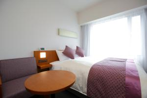 A bed or beds in a room at Hotel Gracery Kyoto Sanjo