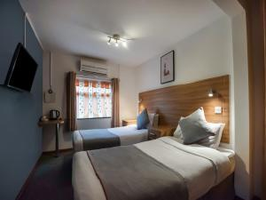 A bed or beds in a room at OYO Arinza Hotel