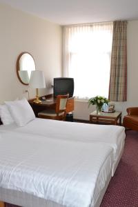 Een bed of bedden in een kamer bij Fletcher Hotel De Zalm