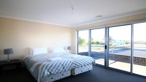 A bed or beds in a room at 'The Anchorage by the Lake'