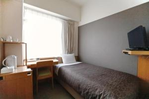 A bed or beds in a room at Tokyo Green Hotel Korakuen