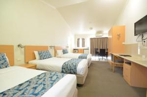 A bed or beds in a room at Boulevarde Motor Inn