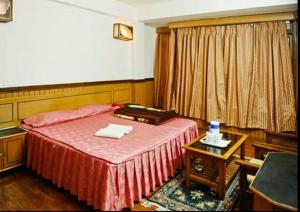 A bed or beds in a room at Hotel Dolma Residency