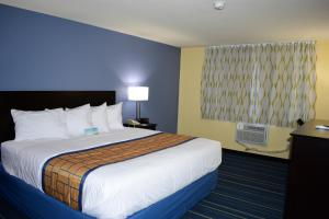 A bed or beds in a room at Days Inn by Wyndham Augusta