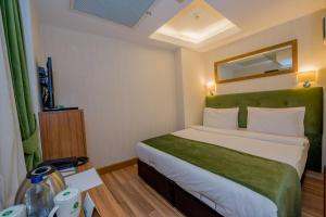 A bed or beds in a room at Bizim Hotel