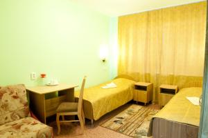 A bed or beds in a room at Molodezhnaya Hotel
