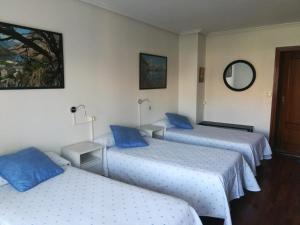 A bed or beds in a room at Pension Toñi
