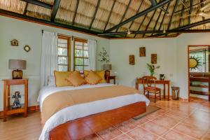 A bed or beds in a room at The Lodge at ChaaCreek