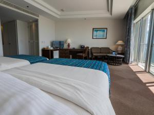 A bed or beds in a room at Kanoa Resort Saipan