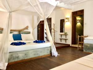 A bed or beds in a room at Zanzistar Lodge