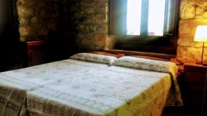 A bed or beds in a room at Hotel Rural Posada Del Monasterio