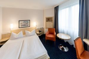 A bed or beds in a room at IntercityHotel Magdeburg