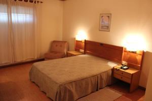 Uma cama ou camas num quarto em Hotel Bom Sucesso