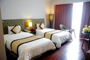 A bed or beds in a room at Muong Thanh Holiday Hue Hotel