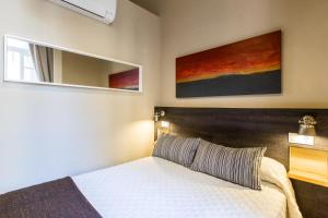 A bed or beds in a room at El Born Guest House by Casa Consell