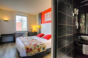 A bed or beds in a room at The Originals Boutique, Hôtel Le Pillebois, Bourg-en-Bresse Nord (Inter-Hotel)