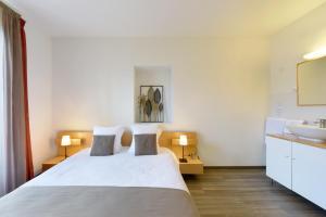 A bed or beds in a room at Hôtel du Marché