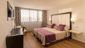 A bed or beds in a room at Hotel Colon Rambla