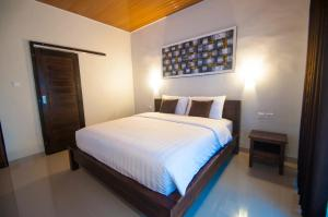 A bed or beds in a room at Sawit Garden Cottages