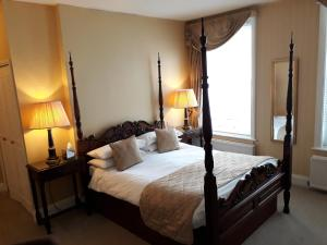 A bed or beds in a room at Powdermills Country House Hotel