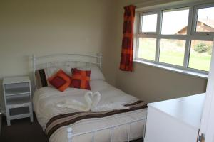 A bed or beds in a room at The Snug - Lakeside bungalow with 2 bedrooms