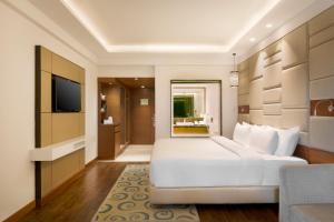 A bed or beds in a room at Radisson Jaipur City Center