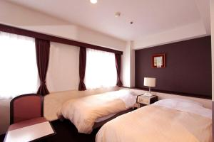 A bed or beds in a room at Kagoshima Kuko Hotel