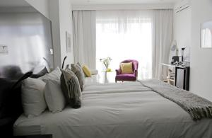 A bed or beds in a room at DysArt Boutique Hotel