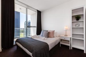 A bed or beds in a room at Casey, South Yarra Private Apartments