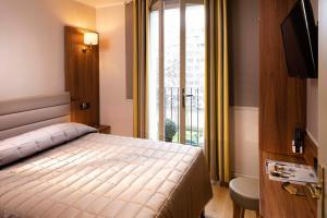 A bed or beds in a room at Hôtel de la Tour Eiffel