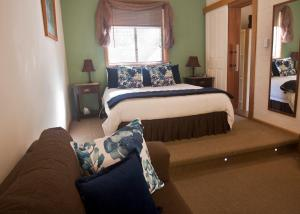 A bed or beds in a room at The Shingles Riverside Cottages