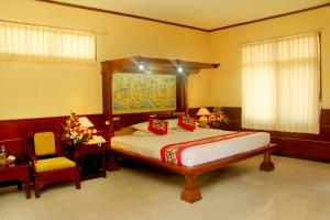 A bed or beds in a room at Melasti Beach Resort & Spa Legian