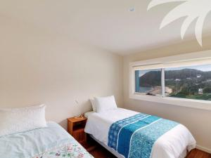 A bed or beds in a room at Cair Paravel at Seal Rocks