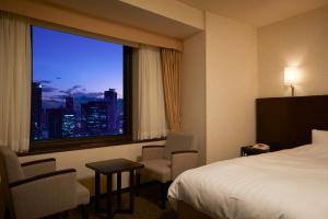 A bed or beds in a room at Osaka Dai-ichi Hotel