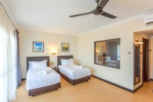 A bed or beds in a room at Camar Resort Langkawi