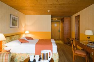 A bed or beds in a room at Hotel & Spa Silberhorn Wengen