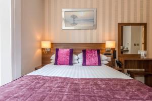 Ein Bett oder Betten in einem Zimmer der Unterkunft London House Hotel