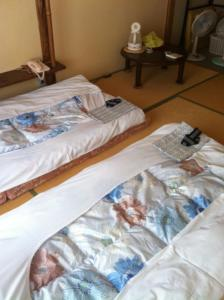 A bed or beds in a room at Rakucho Ryokan