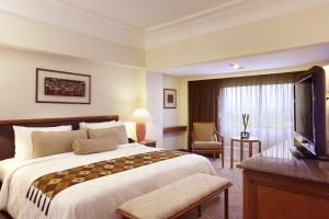 A bed or beds in a room at Aryaduta Menteng