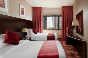 A bed or beds in a room at Frontel Al Harithia Hotel