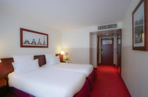 A bed or beds in a room at Hotel Concorde Montparnasse
