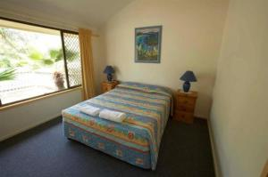 A bed or beds in a room at Wolngarin Holiday Resort Noosa