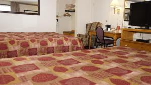 A bed or beds in a room at McIntosh Country Inn & Conference Centre