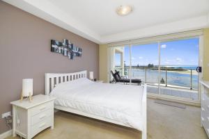 A bed or beds in a room at Ocean Views, Unit 24