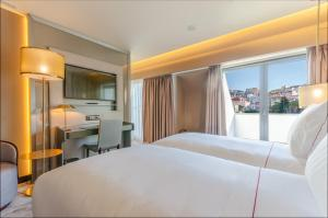 A bed or beds in a room at TURIM Boulevard Hotel