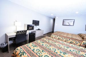 A bed or beds in a room at Belcaro Motel