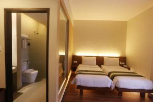 A bed or beds in a room at Grand Whiz Hotel Nusa Dua Bali